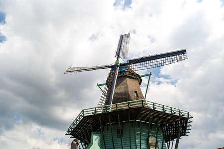 ZAANDAM, NETHERLANDS - JULY 4, 2016 : View of famous windmills in Zaanse Schans village on cloudy sky. Zaandam is popular with windmills.