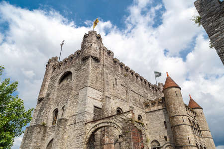 Exterior view of medieval castle named Gravensteen (Castle of the Counts) in Ghent, Belgium on cloudy sky.