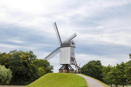 Historical windmill on small hill in nature in Brugge, Belgium.