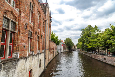 BRUGGE, BELGIUM - JULY 7, 2016 : Tourist boats on Bruges canal in Belgium. Bruges is popular city with touristic attractions.