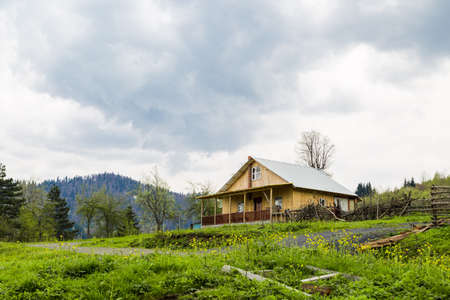plateau: General view of a plateau in meadow area with mountain houses around on cloudy sky.