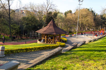 General view of Emirgan Parc with big trees and people hanging around. It is popular with tulip gardens.