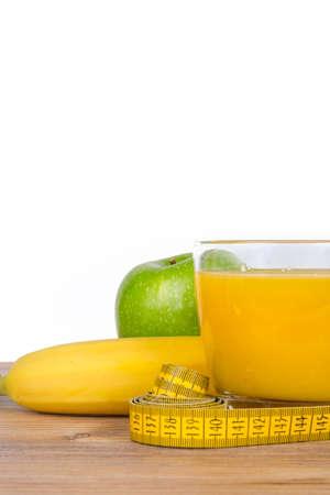 platanos fritos: Plátano, zumo de naranja, manzana verde, concepto sano del ajuste en el fondo de madera, aislado en blanco. Foto de archivo