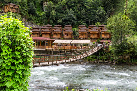 RIZE, TURKEY - AUGUST 17, 2016 : General landscape view of wooden draw bridge on Firtina River in Camlihemsin, Rize, Turkey among green trees.