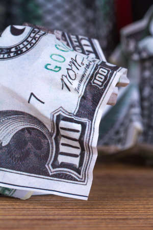 Dollar banknotes crumpled inside garbage basket, rubbish bin focused on consuming money in finance concept, on wooden background.