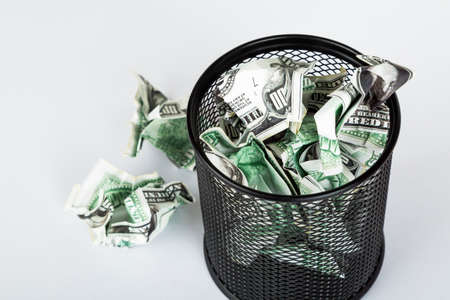 Dollar banknotes crumpled inside garbage basket, rubbish bin focused on consuming money in finance concept, isolated on white background.