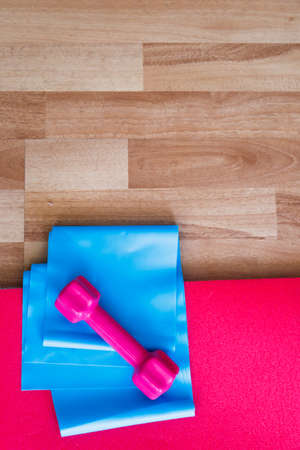 Rubber band and pink dumbbell on pilates or yoga mat, healthy life and sport concept, wooden background. Banco de Imagens