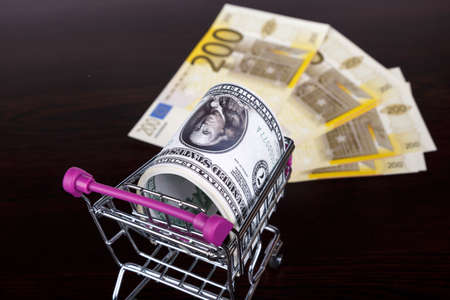 Stack of dollar and euro banknotes with shopping cart in money consuming concept.