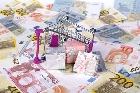 Stack of Euro banknotes with shopping cart and gift boxes in money consuming concept, on full background. Stock Photo