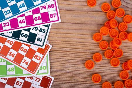 Colorful lotto or bingo game papers with numbers and plastic lotto barrels, on wooden background.