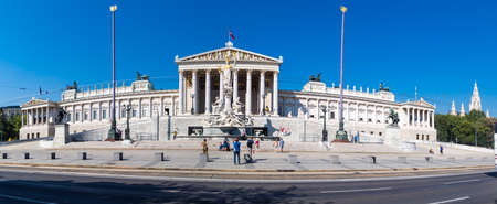 VIENNA, AUSTRIA - SEPTEMBER 12, 2016 : Panoramic view of Austrian Parliament building with famous Pallas Athena fountain with statues on. Parliament building was built in late 1880s by architect Theophil Hansen, on blue sky background. Editorial