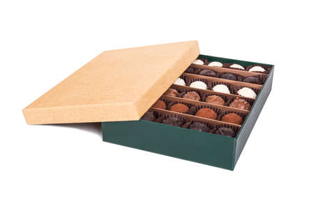 View of yummy tasty white, dark and milky chocolate balls in green box, isolated on white background.