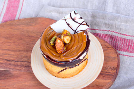 Yummy tasty cake with cream, nuts and caramel sauce, served with almonds. Stock Photo