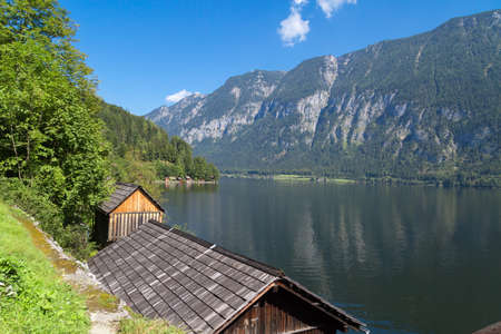 Landscape view of wooden mountain houses along lakeside among Austrian Alp mountains in Salzkammergut on blue sky background.