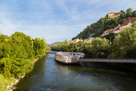 GRAZ, AUSTRIA - SEPTEMBER 16, 2016 : Exterior view of Murinsel Bridge in Graz. Designed modern architecture artificial island on Mur river with trees around in spring.