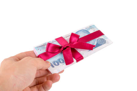 Stack of Turkish lira banknotes wrapped with ribbon as a gift on hand, isolated on white background. Stock Photo