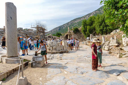 EPHESUS, TURKEY - JUNE 20, 2018 : Ruins in historical ancient city Ephesus with restoration and tourists around on cloudy sky in Izmir, Turkey. Editorial
