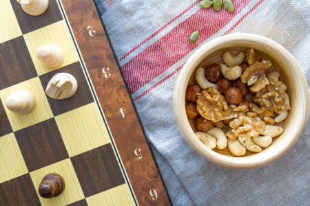 Healthy eating concept. Mix of dried fruits and nuts with chess pieces on squared strategy game table. 写真素材 - 104617825