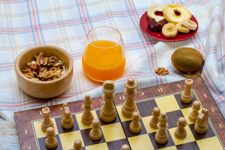 Healthy eating concept. Mix of dried fruits and nuts with chess pieces on squared strategy game table. 写真素材 - 104589721