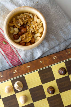 Healthy eating concept. Mix of dried fruits and nuts with chess pieces on squared strategy game table.
