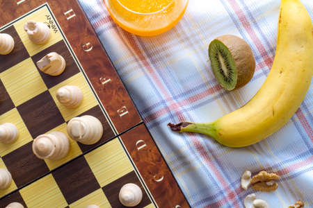 Healthy eating concept. Mix of dried fruits and nuts with chess pieces on squared strategy game table. 写真素材 - 104590070