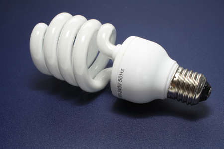 Economical fluorescent lamp. Close-up. On a dark background. photo