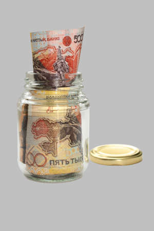 Money Kazakhstan. Packed in a glass jar. Close-up. Isolation on a gray background. photo