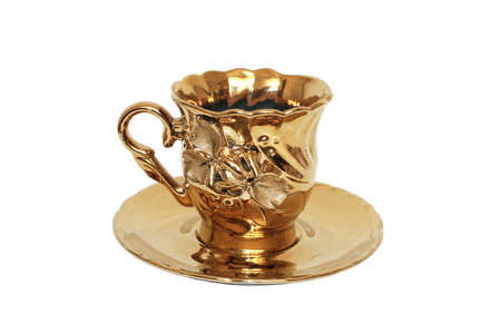 Teacups color of gold. Close-up. Isolated on white background. photo