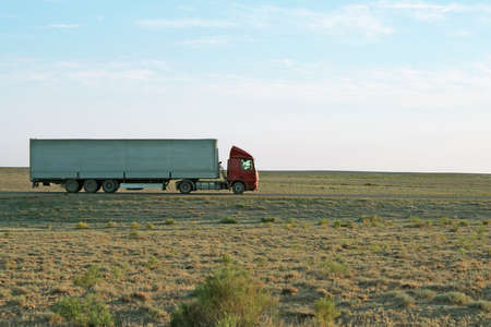 Lone van driving through the steppe road. Stock Photo