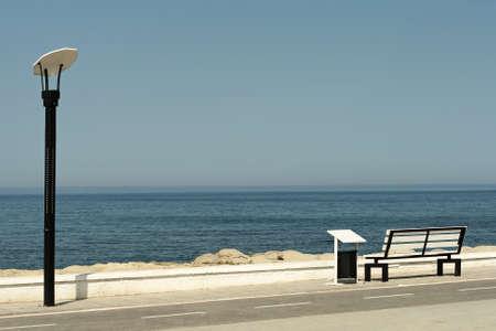 streetlamp: Empty bench overlooking the ocean Stock Photo