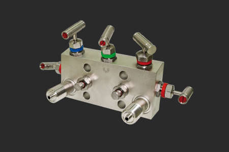 manifold: Manifold block for the differential sensor. Isolated on a dark gray background. Stock Photo