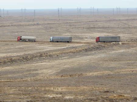 Trucks go around a closed road section. Tipper mountainous terrain. Mangistau region. Kazakhstan. Stock Photo