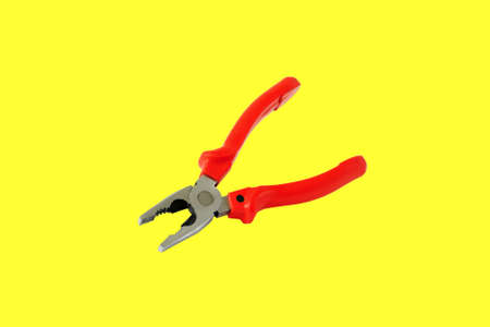 Pliers with red handles.  Isolated on a yellow background. Stock Photo
