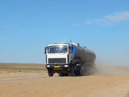 Tanker truck driving on dusty dirt road.