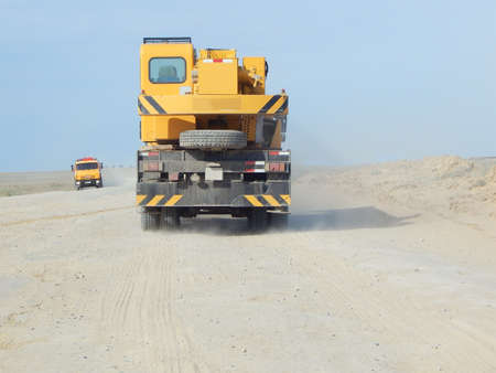 Mobile crane travels along a dusty dirt road. Stock Photo