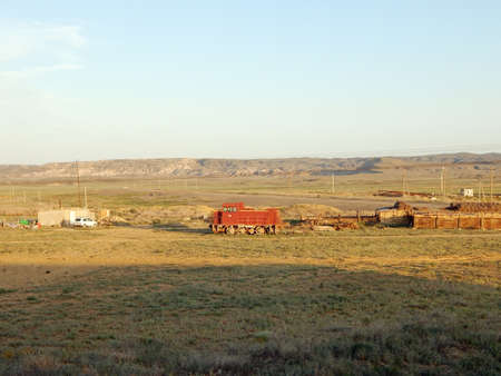 Old locomotive standing on the ground on a background of a steppe landscape.