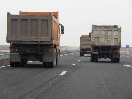 Dump trucks on the road. Mangistau region. Kazakhstan. Stock Photo