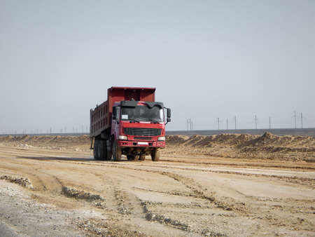 Red dumper in the desert, laying a new road. Kazakhstan.