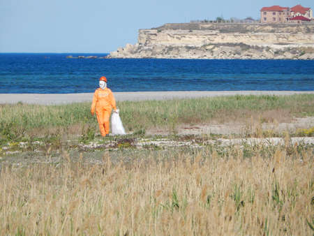 Worker in orange overalls is cleaning the beach. Kazakhstan. Aktau. Stock Photo