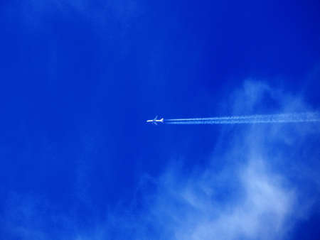 Plane is high in the blue sky.