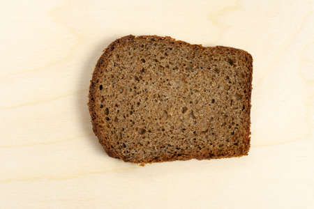 Slice of bread on a wooden background. Stock Photo