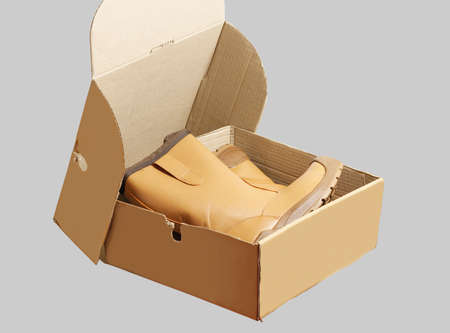 Orange work shoes in a cardboard box. Stock Photo