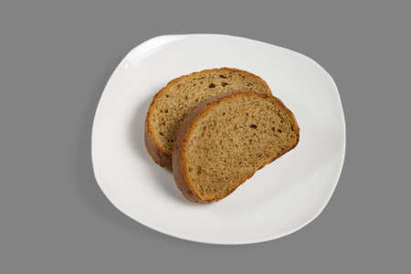 Slices of bread on a white plate. Isolated on gray background. Stock Photo
