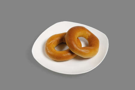 Bagels on a white plate. Isolated on gray background.