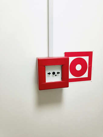 Red fire alarm button on the white wall. 写真素材
