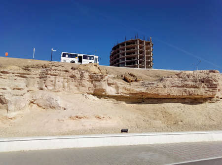 Unfinished house on the rock and the bus. Kazakhstan. Aktau. 写真素材