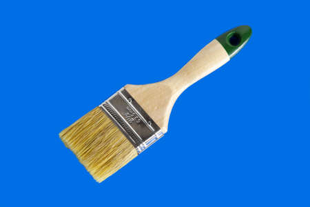 Round paint brush. Close-up on a blue background.