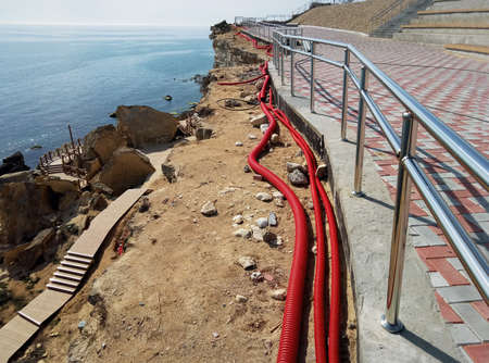 Construction on the rocks. Cable routing in red corrugations. Observation deck on the rocks. Coast of the Caspian Sea. Kazakhstan. Aktau 01 May 2019 year. 写真素材