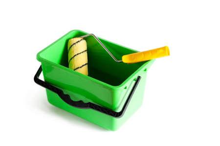 Rouleau à peinture dans un seau en plastique vert. Fermer. Isolé sur fond blanc.