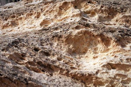 Surface sandy rock. Rocky shore of the Caspian Sea.